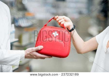 Pharmacist Giving First Aid Kit To The Woman Client In The Pharmacy Store, Close-up View