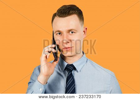 Portrait Of Young Businessman Dressed In Blue Shirt And Tie Talking On The Mobile Phone, Isolated On