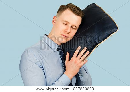 Young Businessman Dressed In Blue Shirt And Tie, Sleeps On The Pillow , Isolated On Blue Background