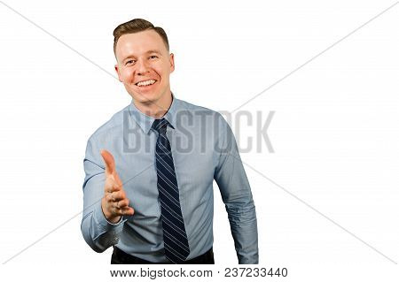 Young Businessman Dressed In Blue Shirt And Tie, Extends A Hand For A Handshake, Isolated On White B