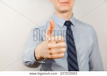 Young Businessman Dressed In Blue Shirt And Tie Shows Thumb Up Close Up, On Gray Background