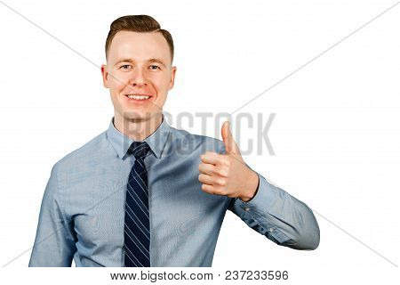 Young Businessman Dressed In Blue Shirt And Tie Shows Thumb Up, Isolated On White Background