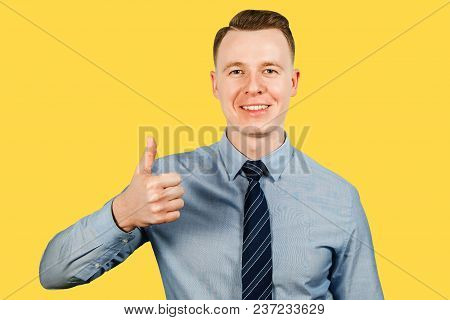 Young Businessman Dressed In Blue Shirt And Tie Shows Thumb Up, Isolated On Yellow Background