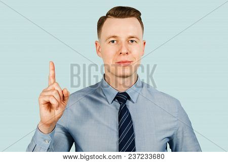 Young Businessman Dressed In Blue Shirt And Tie Shows Index Finger Up, Isolated On Blue Background