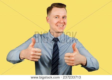 Young Businessman Dressed In Blue Shirt And Tie Shows Thumbs Up And Smiles, Isolated On Yellow Backg