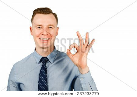 Young Businessman Dressed In Blue Shirt And Tie Shows Ok Sign, Isolated On White Background