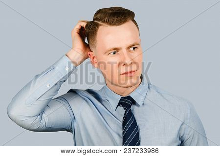 Young Businessman Dressed In Blue Shirt And Tie Scratches His Head, Isolated On Blue Background