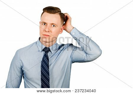 Young Thinking Businessman Dressed In Blue Shirt And Tie Scratches His Head, Isolated On White Backg