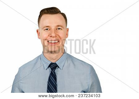 Portrait Of Young Smiling Businessman Dressed In Blue Shirt And Tie, Isolated On White Background