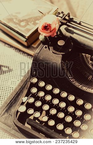 Vintage Typewriter With Pink Rose , Old Book On Table. Sepia Photo