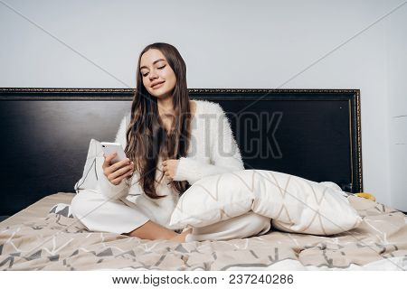 Lovely Long-haired Girl In White Pajamas Sits On The Bed, Looks Into Her Smarthrobe And Smiles
