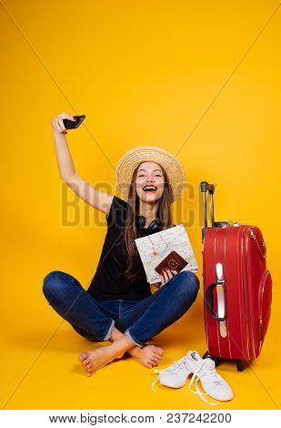 Happy Young Girl In A Hat Goes On Vacation With A Large Suitcase, Keeps Tickets For The Plane And Ma
