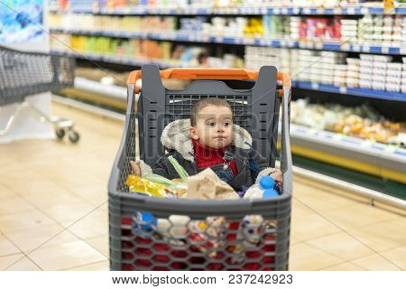 Full Cart With Food In The Supermarket. In The Cart Sits A Baby.