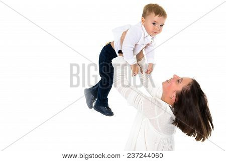 Happy Smiling Loving Mother And Her Baby Is Playing On A White Background. Mom Throws The Baby In He