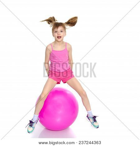 A Little Girl Is Jumping On A Big Ball For Fitness. The Concept Of Sport And A Healthy Lifestyle. Is