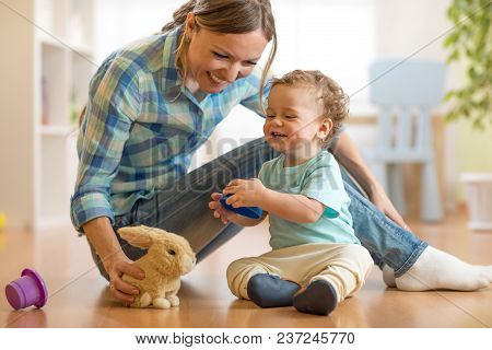 Mother Plaing With Her Son Baby In Nursery