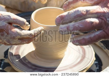 Adult Hand Fed Baby's Hands To Work With A Potter's Wheel