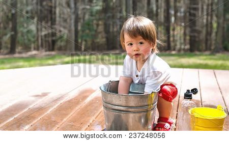 Happy Toddler Boy Playing Outside With Buckets Of Water