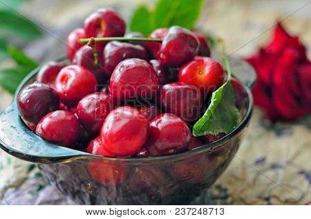 Cherries In Glass Bowl. Red Cherry And Leaf In Bowl And Napkin On Wooden Background With Sunlight. F