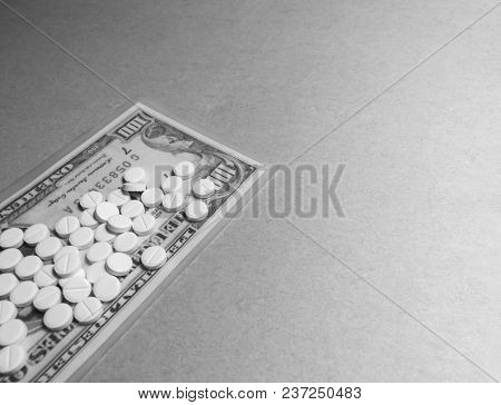 A Black And White Photo Of Tablets On One Hundred Dollar Bill On The Gray Background With Copy Space