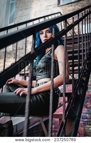 Lovely Blue-haired Rock Girl (informal Model), Dressed In The Black Leather Pants And Topic Sits On