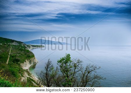 Blue Sea. Waves Reach The Coast, Which Consists Of Rocks. Ships Enter The Port In The Distance