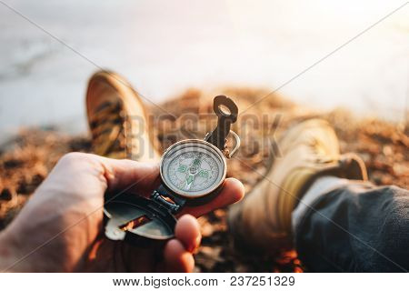 Hipster Traveler Sitting And Hold In Hand Compass. Pov View. Blurred Background. Flare Effect