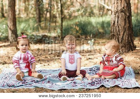 Kids In Traditional Ukrainian Clothes Play In Forest In Sunbeam. Boy And Two Girls