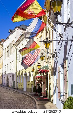 Old Paved Street With Street Lights And Flags Of Germany, Usa, Russia And Spain, Hanging On Colorful