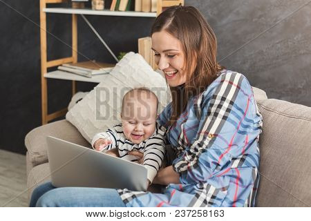 Beautiful Business Mom Working On Laptop In Office While Spending Time With Her Cute Baby. Business,