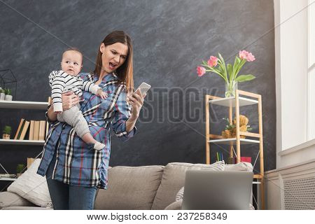 Angry Mother Working At Home Office With Her Baby. Young Woman Using Smartphone While Spending Time