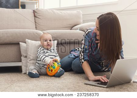 Happy Business Mom Working On Laptop In Home Office While Spending Time With Her Cute Baby, Lying On