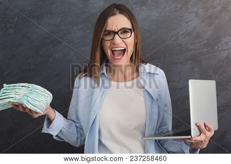 Angry Businesswoman Holding Laptop And Diapers On Grey Background, Crop. Young Working Mother Has No