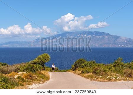 Unidentified Tourists Walking Along A Road With A View Of The Sea And Kefalonia Island In Distance.