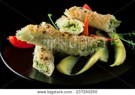 Puff Pastry With Spinach And Cheese Filling On A Black Plate And Black Background.