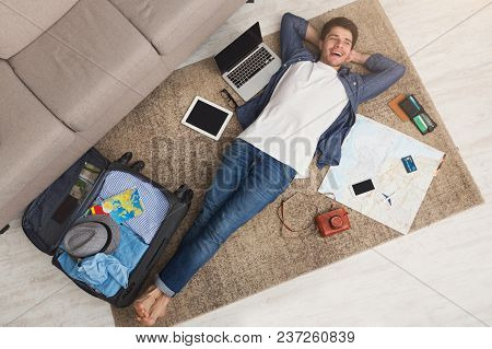 Young Cheerful Man Dreaming About Travel Around World, Lying On Floor With Blank Laptop, Tablet, Sma