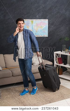 Young Cheerful Man Walking With Packed Suitcase And Talking On Mobile Phone, Ready For Annual Vacati