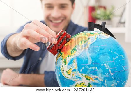 Young Cheerful Man Dreaming About Bus Travel Around World, Looking At Globe At Home. Handsome Guy Pl