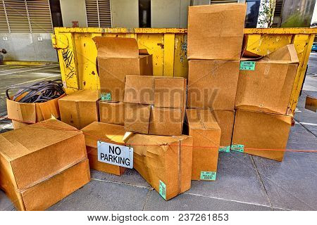 A closeup view of stacks of cardboard boxes with a no parking sign next to a yellow trash dumpster.