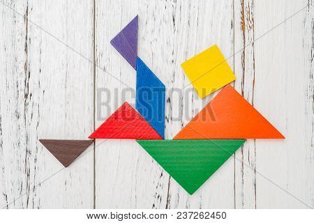 Wooden Tangram Shaped Like A People Having A Bicycle Kick