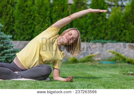 Beautiful Pregnant Woman In Yellow T-shert Doing Prenatal Yoga On Nature Outdoors. Sport, Fitness, H