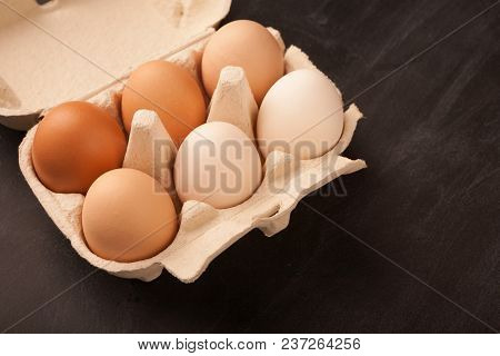 Gradient Of Natural Colored Eggs Arranged In Organic Paper Container On Black Background. Minimalist