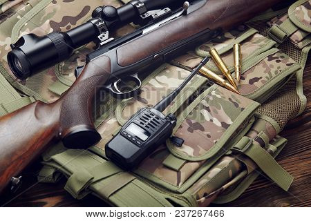 Hunting rifle with optical sight and equipment.