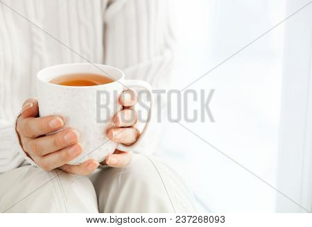 Woman's Hands Is Holding Hot Cup Of Coffee Or Tea In Morning Sunlight.