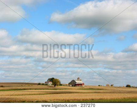 Farm House And Fields Under Blue Sky