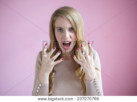 Portrait of furious young businesswoman with red nails and wavy fair hair screaming, keeping mouth widely and making angry gesture, being mad at her ineffective employees. Anger, fury and rage concept poster