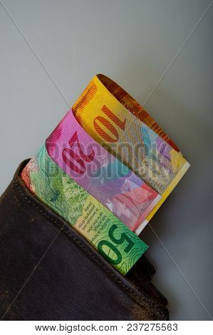 Swiss Cash Paper Denominations - Ten, Twenty, Fifty Francs Are In An Old Wallet. The Purse With Mone
