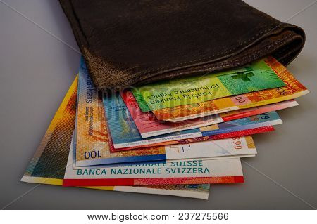 Swiss Cash Paper Bills Are In The Old Wallet. The Purse With Switzerland Francs Lies On A Light Back