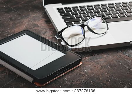 E-book And Paper Books On The Table With A Cup Of Coffee, A Laptop And Reading Glasses. Concepts Of