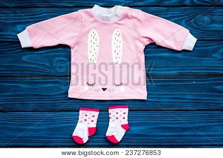 Clothes For Newborn And Small Children On Blue Wooden Background Top View. Clothes For Girl Space Fo